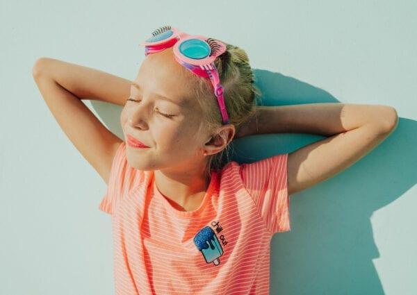 Meisje dat geniet van de zon en heeft een roze kat-vormige zwembril aan.