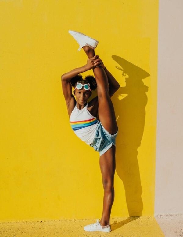 Lenig meisje die haar rechterbeen hoog in de lucht steekt. Ze draagt een wit kat-vormige zwembril.