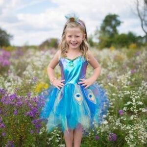 Pretty Peacock Dress is voorbestemd om een van de meest favoriete speelkameraadjes te worden! Het lijfje is gemaakt van tricot en spandex, waardoor het zacht, comfortabel en rekbaar is. Gecombineerd met elastische fluweel en spandex aan de achterkant, is deze jurk nog comfortabeler. Het holografische effect is verbluffend, want het creëert deze levendige kleurrijke jurk. De top is versierd met sierlijke blauwe en gouden biesjes en is voorzien van een grote glinsterende edelsteen omlijst met gouden accenten. De veelkleurige rok is gemaakt met lagen van zachte tule en is voorzien van zes pauwenveren met glitter, bedrukt met iconische pauwen details. De hoofdband is gewikkeld in dezelfde zachte gebreide stof en is versierd met een glinsterende edelsteen en glitter tule accenten.