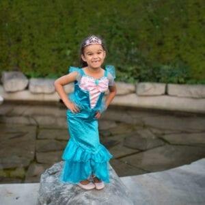 Meisje met blauwe zeemeermin jurk. Het is een zeemeerminnenjurk met een roze satijnen top. Heeft glitter schubben op de rok en is afgewerkt met organza.