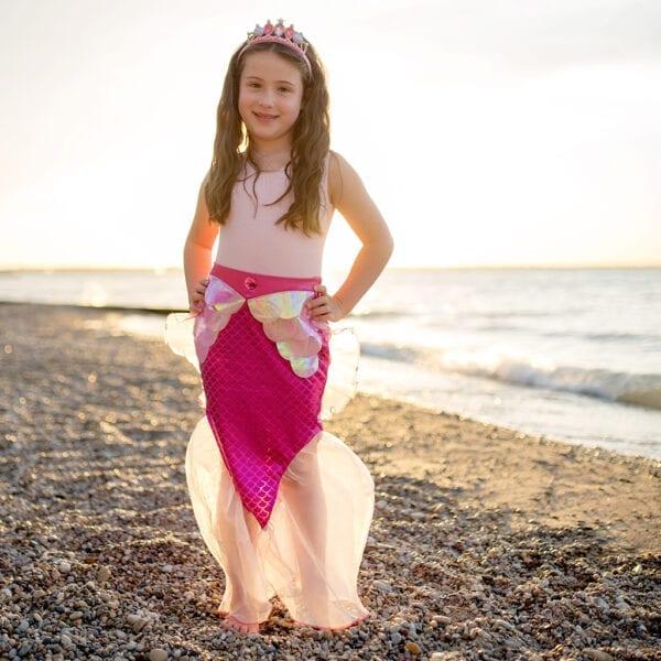 Een meisje met een roos zeemeermin rokje aan. Het zeemeermin rokje heeft licht roze schubben en is onderaan mooi afgewerkt met tule. Ze draag een zeemeermin tiara op haar hoofd.