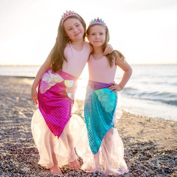 Twee meisjes aan het strand. Ze hebben beide een zeemeermin rokje aan. Het is een roos en blauw zeemeermin rokje. Ze dragen beide een zeemeermin tiara. De zeemeerminnenstaarten zijn onderaan mooi afgewerkt met tule.